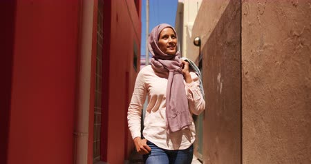 головной платок : Front view of a young mixed race woman wearing a hijab walking in a city street, looking around and smiling