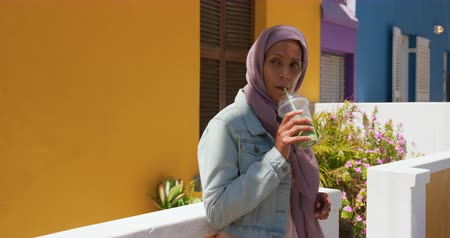 boş zaman : Front view of a young mixed race woman wearing a hijab in a city street, drinking juice and leaning against a wall with colourful houses in the background