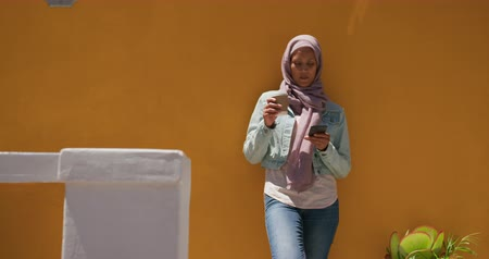 İslamiyet : Front view of a young mixed race woman wearing a hijab in a city street, using a smartphone, drinking coffee and leaning against a yellow wall in the background