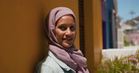 spare : Portrait of a young mixed race woman wearing a hijab in a city street, smiling to camera with a yellow wall in the background