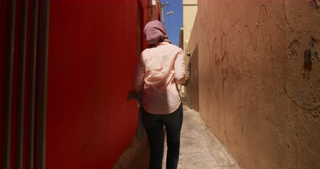 spare : Rear view of a young mixed race woman wearing a hijab walking in a city street, looking around Stock Footage