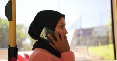 sobressalente : Side view of a young mixed race woman wearing a hijab commuting sitting on a bus in a city, talking on the smartphone
