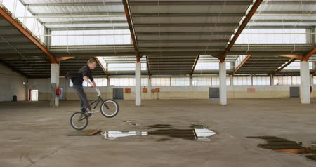 bmx : Side view of a young Caucasian man jumping over a puddle on a BMX bike while practicing tricks in an abandoned warehouse Stock Footage
