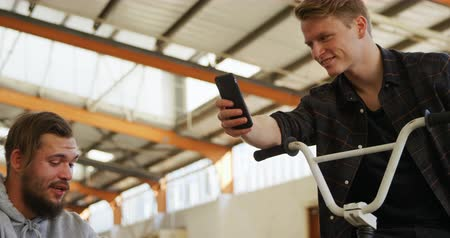 bmx : Front view close up of two young adult Caucasian men sitting on BMX bikes talking to each other and using smartphones in an abandoned warehouse