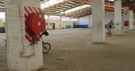 bmx : Side view of two young Caucasian men riding BMX bikes around the columns in an abandoned warehouse