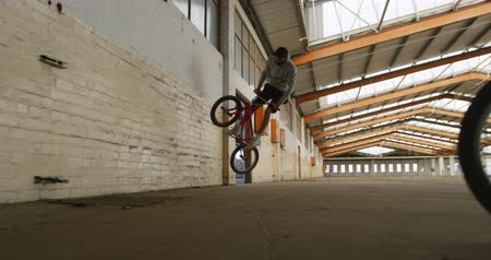 bmx : Front view of two young Caucasian men wallriding on BMX bikes in an abandoned warehouse Stock Footage