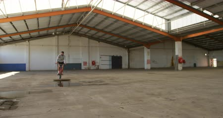 bmx : Front view of a young Caucasian man jumping over a puddle on a BMX bike while practicing tricks in an abandoned warehouse
