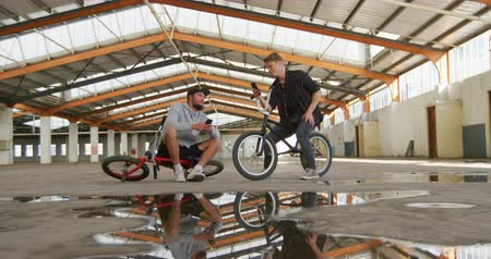 passatempos : Front view of two young adult Caucasian men sitting on BMX bikes talking to each other and using smartphones in an abandoned warehouse Stock Footage