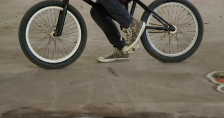 bmx : Side view of a young adult Caucasian man sitting on a BMX bike using a smartphone in an abandoned warehouse