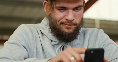 rebelde : Front view close up of a young adult Caucasian man with a beard sitting and using a smartphone in an abandoned warehouse Vídeos