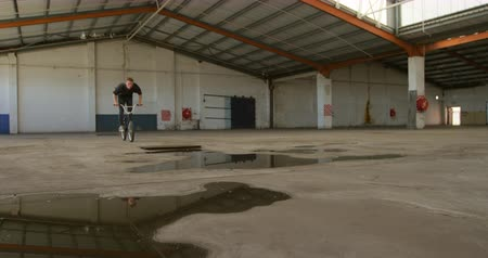 vocação : Front view of a young Caucasian man jumping over a puddle on a BMX bike while practicing tricks in an abandoned warehouse