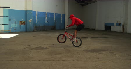 bmx : Side view of a young Caucasian man jumping, turning and balancing on the back wheel of a BMX bike while practicing tricks in an abandoned warehouse Stock Footage