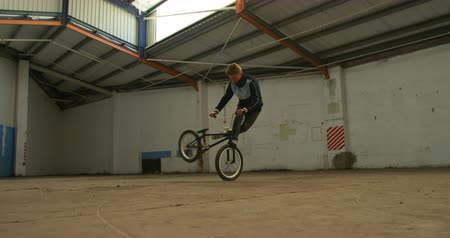 vocação : Side view of a young Caucasian man jumping and turning on a BMX bike while practicing tricks in an abandoned warehouse