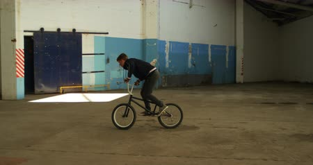 bmx : Side view of a young Caucasian man jumping on a BMX bike while practicing tricks in an abandoned warehouse