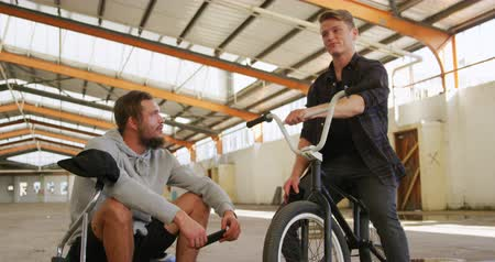 bmx : Front view of two young adult Caucasian men sitting on BMX bikes talking to each other in an abandoned warehouse