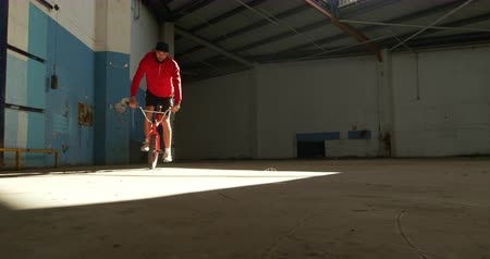 bmx : Front view of a young Caucasian man balancing on the front wheel of a BMX bike in a shaft of sunlight while practicing tricks in an abandoned warehouse