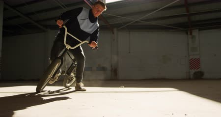 bmx : Side view of a young Caucasian man sliding on a BMX bike in a shaft of sunlight while practicing tricks in an abandoned warehouse Stock Footage