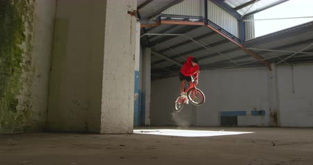 bmx : Front view of a young Caucasian man jumping on a BMX bike in a shaft of sunlight while practicing tricks in an abandoned warehouse Stock Footage