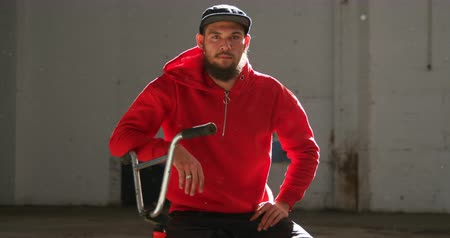 bmx : Portrait of a young Caucasian man with a beard wearing a baseball cap and a red top sitting on a BMX bike looking to camera in an abandoned warehouse, backlit by sunlight