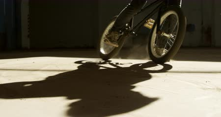 bmx : Rear view close up of a young Caucasian man skidding on a BMX bike in a shaft of sunlight while practicing tricks in an abandoned warehouse Stock Footage