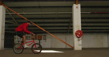 vocacion : Side view of a young Caucasian man jumping on a BMX bike in a shaft of sunlight while practicing tricks in an abandoned warehouse Archivo de Video
