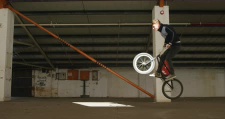 bmx : Side view of a young Caucasian man jumping on a BMX bike in a shaft of sunlight while practicing tricks in an abandoned warehouse Stock Footage
