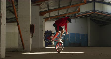 bmx : Side view of a young Caucasian man balancing on the front wheel of a BMX bike in a shaft of sunlight while practicing tricks in an abandoned warehouse Stock Footage