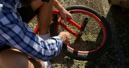 vocação : Overhead low section view of a young Caucasian man repairing the wheel of his BMX bike