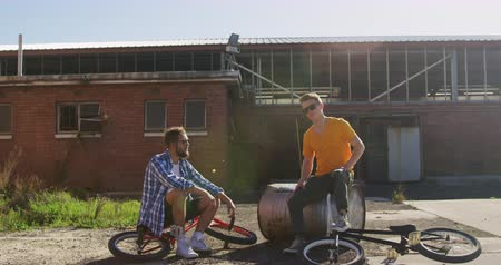 bmx : Front view of two young Caucasian men wearing sunglasses sitting with BMX bikes talking outside an abandoned warehouse in the sun