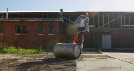 quadris : Side view of a young Caucasian man wearing sunglasses jumping and turning on a barrel on a BMX bike outside an abandoned warehouse in the sun