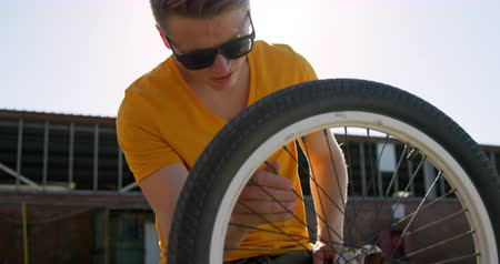 bmx : Front view close up of a young Caucasian man wearing sunglasses doing maintenence to the wheel of his BMX bike outside in the sun