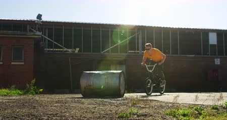 bmx : Front view of a young Caucasian man wearing sunglasses jumping over a barrel on a BMX bike outside an abandoned warehouse in the sun