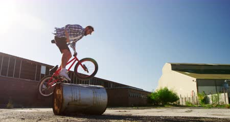bmx : Front view of a young Caucasian man wearing sunglasses jumping and turning on a barrel on a BMX bike outside an abandoned warehouse in the sun