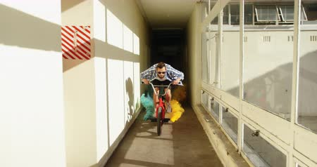 bmx : Front view of a young Caucasian man wearing sunglasses riding a BMX bike with green and orange smoke grenades attached to it and jumping in a narrow corridor at an abandoned warehouse in the sun