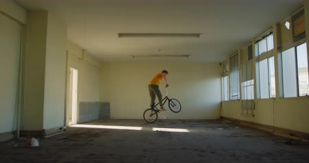 bmx : Side view of a young Caucasian man turning in the air on a BMX bike in a shaft of sunlight while practicing tricks in an abandoned warehouse
