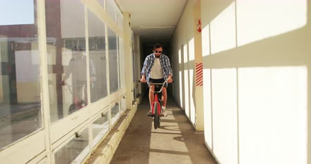 bmx : Front view of a young Caucasian man wearing sunglasses jumping on a BMX bike in a narrow corridor at an abandoned warehouse in the sun Stock Footage