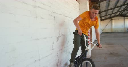 bmx : Front view of a young Caucasian man wallriding on a BMX bike in an abandoned warehouse
