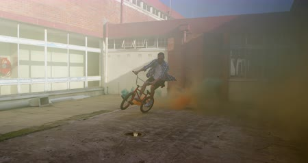 granada : Side view of a young Caucasian man jumping on a BMX bike with a blue and orange smoke grenade attached to it, outside an abandoned warehouse