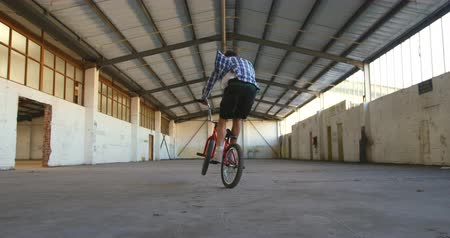 back side : Side view of a young Caucasian man jumping, turning and balancing on the back wheel of a BMX bike while practicing tricks in an abandoned warehouse Stock Footage
