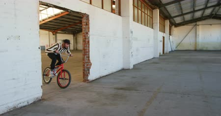 bmx : Side view of two young Caucasian men riding their BMX bikes and practicing tricks in an abandoned warehouse
