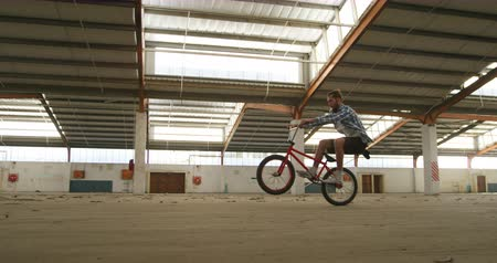 bmx : Side view of two young Caucasian men riding balancing on the back wheels of their BMX bikes while practicing tricks in an abandoned warehouse
