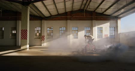 granada : Side view of a young Caucasian man jumping on a BMX bike with a grey smoke grenade attached to it, in an abandoned warehouse Vídeos