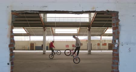 bmx : Side view of two young Caucasian men riding their BMX bikes in opposite directions and jumping while practicing tricks in an abandoned warehouse Stock Footage