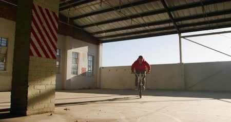 bmx : Front view of a young Caucasian man riding a BMX bike and jumping  while practicing tricks in an abandoned warehouse