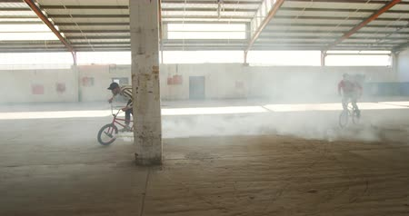 granada : Side view of two young Caucasian men jumping and riding on BMX bikes, one with a grey smoke grenade attached to it, in an abandoned warehouse Vídeos