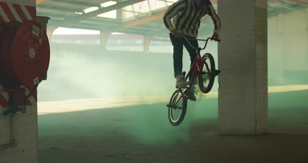 granada : Front view of two young Caucasian men jumping and riding on BMX bikes in an abandoned warehouse, with a green smoke grenade attached to it Vídeos