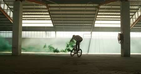 сосредоточиться на переднем плане : Side view of a young Caucasian man jumping on a BMX bike with a green smoke grenade attached to it, in an abandoned warehouse, another sihouetted BMX rider passes in the foreground Стоковые видеозаписи