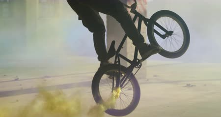 granada : Side view of two young Caucasian men riding and doing tricks on BMX bikes with blue and yellow smoke grenades attached to them, in an abandoned warehouse