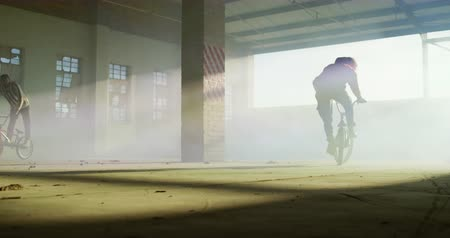 granada : Front view of two young Caucasian men riding and doing tricks on BMX bikes with blue and yellow smoke grenades attached to them, in an abandoned warehouse Vídeos
