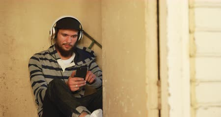 перемычка : Front view of a hip young Caucasian man wearing a baseball cap and headphones sitting on the floor leaning against a wall in an abandoned warehouse, holding a smartphone and listening to music Стоковые видеозаписи